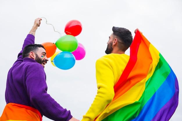 Gay con bandiera arcobaleno e palloncini che si godono la sfilata Foto Gratuite