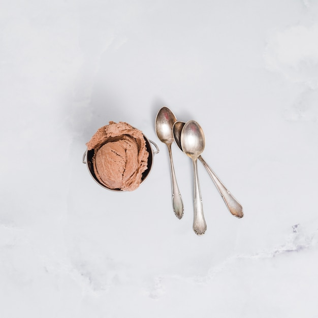 Gelato al cioccolato in una ciotola con cucchiai sulla superficie del marmo Foto Gratuite