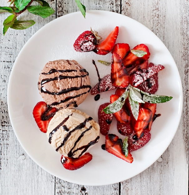 Gelato con fragole e cioccolato su un piatto bianco Foto Gratuite