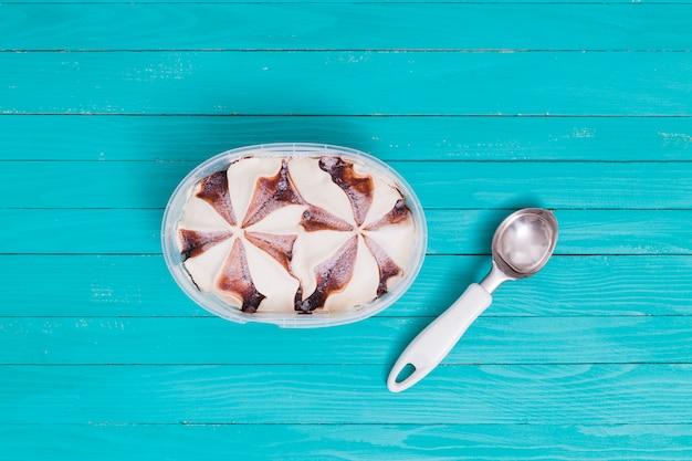 Gelato in contenitore con cucchiaio su superficie di legno Foto Gratuite