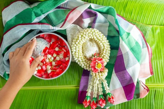 Gelsomino e ghirlanda di rose bianche sullo sfondo di foglie di banana verde. Foto Premium