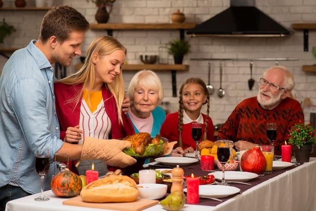 Generazioni familiari che sentono l'odore del tacchino cotto fresco Foto Gratuite