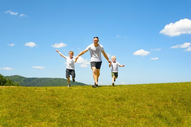 Generi con due bambini piccoli che corrono congiuntamente sul campo verde Foto Premium