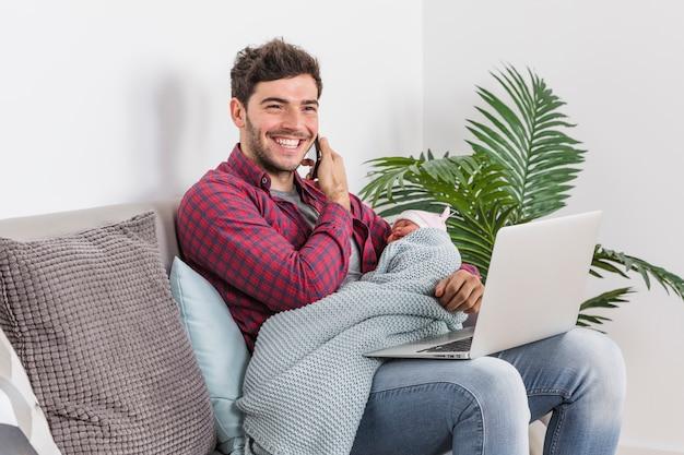 Generi con il bambino che parla sul telefono e che per mezzo del computer portatile Foto Gratuite