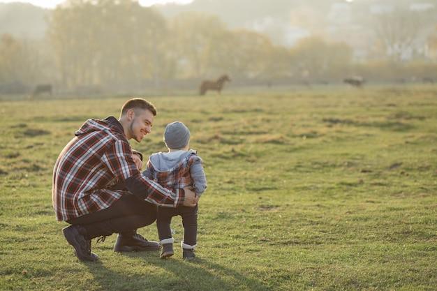 Generi con il piccolo figlio che cammina in un campo di mattina Foto Gratuite