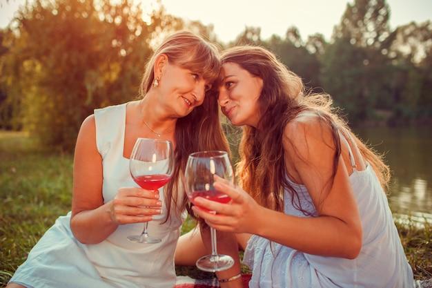 Generi il vino bevente con sua figlia adulta dal fiume dell'estate al tramonto. Foto Premium
