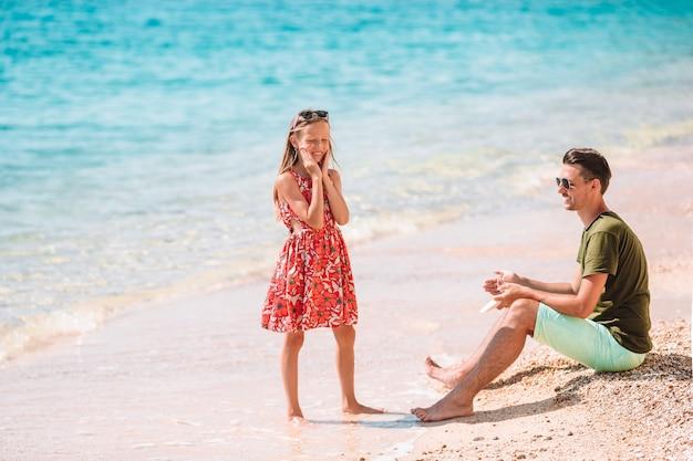 Generi l'applicazione della crema di protezione del sole a sua figlia alla spiaggia tropicale Foto Premium