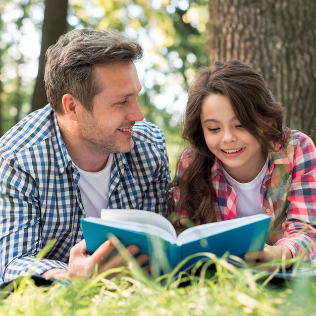Generi l'esame della sua figlia mentre leggono il libro in parco Foto Gratuite