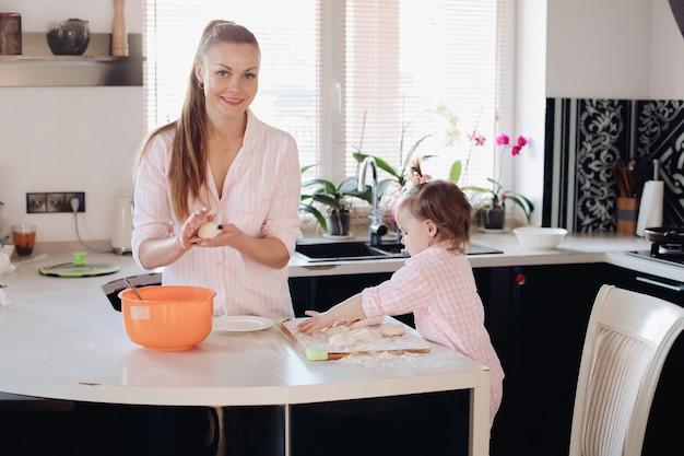 Genitore d'aiuto del piccolo bambino adorabile con pasta alla cucina Foto Premium