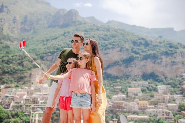Genitori e bambini che prendono selfie foto sulla città di positano in italia sulla costiera amalfitana Foto Premium