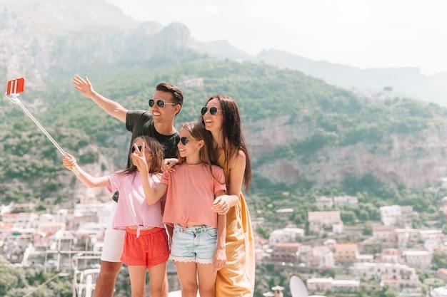 Genitori e figli che prendono selfie foto di sfondo positano città in italia sulla costiera amalfitana Foto Premium