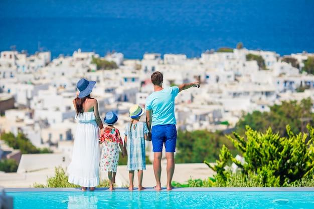 Genitori e figli sullo sfondo della piscina all'aperto città di mykonos cicladi, in grecia Foto Premium
