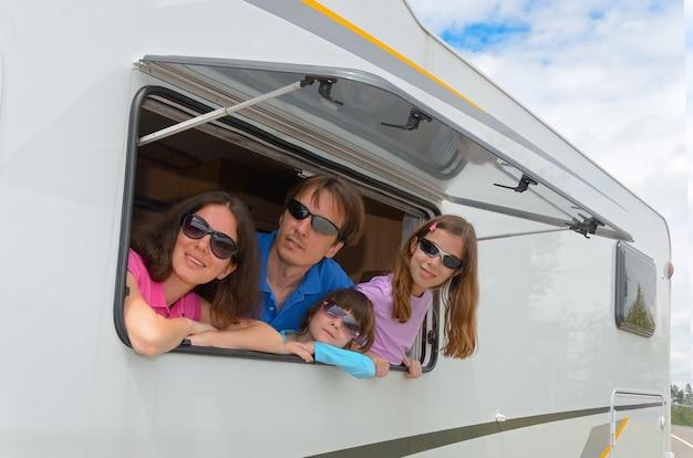 Genitori felici che viaggiano con bambini e si divertono in camper Foto Premium