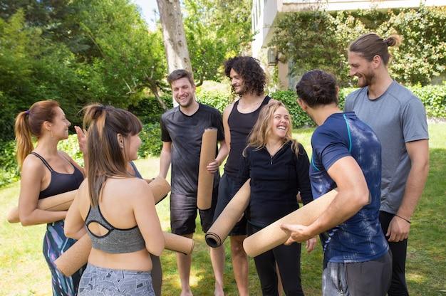 Gente allegra con stuoie di yoga chiacchierando e ridendo Foto Gratuite