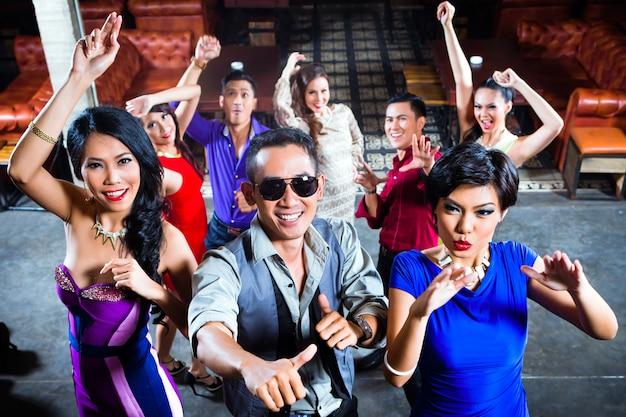Gente asiatica che fa festa sulla pista da ballo in discoteca Foto Premium
