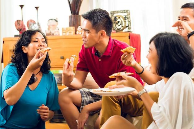 Gente asiatica che mangia pizza alla festa Foto Premium