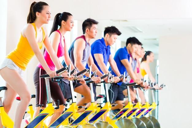 Gente asiatica nell'addestramento della bici di filatura alla palestra di forma fisica Foto Premium