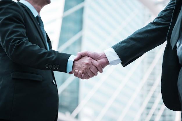 Gente di affari che agita le mani, concetto di affare di saluto, fondo moderno della città. Foto Premium