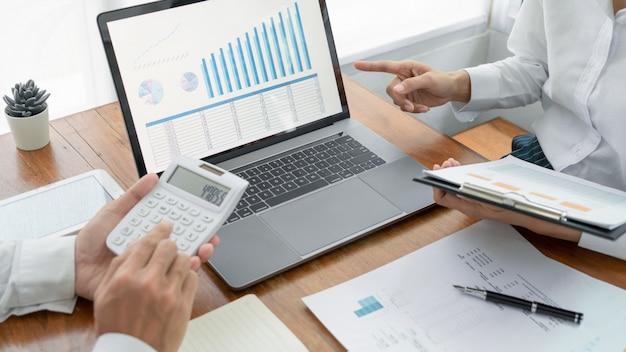 Gente di affari che parla discutendo con la pianificazione del collega che analizza i grafici di dati del documento finanziario Foto Premium