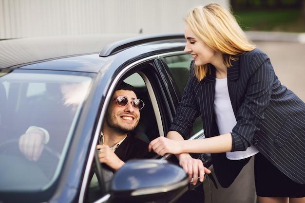 Gente di affari che parla vicino al parcheggio. l'uomo con gli occhiali è seduto in macchina, la donna è in piedi accanto a lui Foto Premium