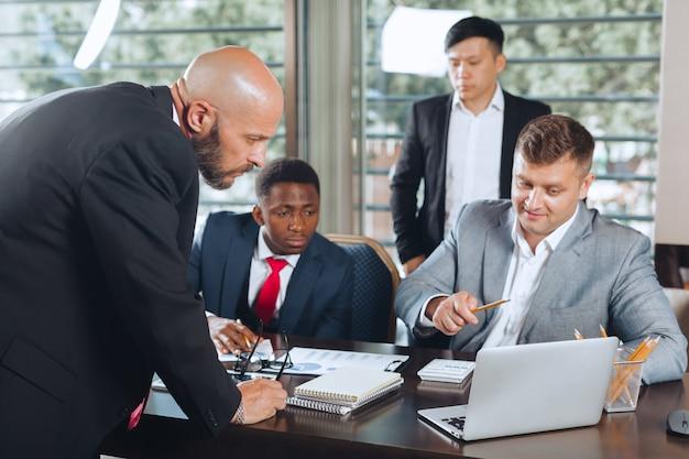 Gente di affari che si incontra intorno ad un tavolo della sala del consiglio che discute strategia Foto Premium