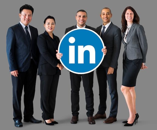 Gente di affari che tiene un logo di linkedin Foto Gratuite