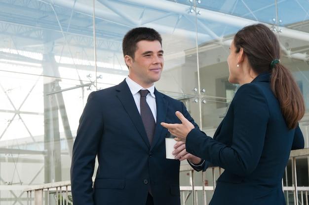 Gente di affari contenta che gesturing e che chiacchiera all'aperto Foto Gratuite
