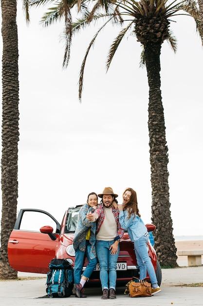 Gente felice che prende selfie vicino all'automobile rossa Foto Gratuite