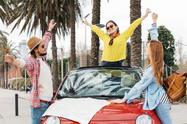 Gente felice che sta vicino all'automobile con la mappa stradale Foto Gratuite