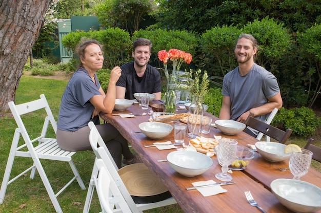 Gente felice facendo colazione al tavolo di legno nel cortile Foto Gratuite