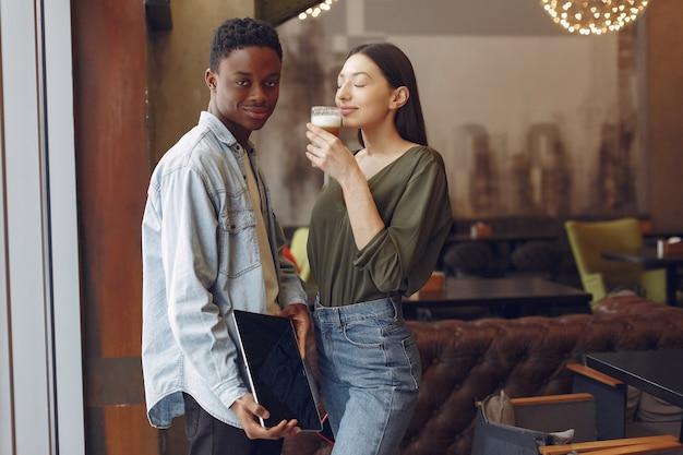 Gente internazionale in piedi in un caffè con tablet e caffè Foto Gratuite