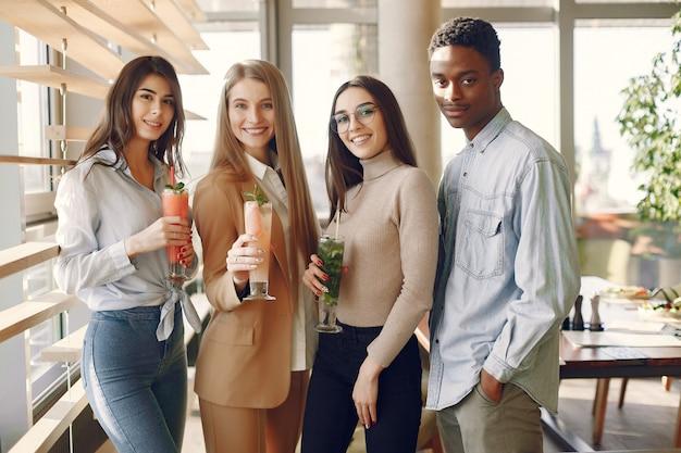 Gente internazionale in piedi in un caffè e bere un cocktail Foto Gratuite