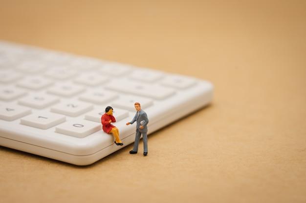Gente miniatura che si siede sul calcolatore bianco facendo uso come concetto di affari del fondo Foto Premium