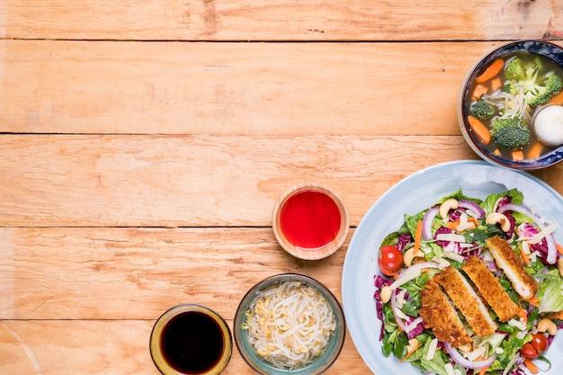 Germogli di fagiolo; la minestra; filetto; insalata con salse sulla scrivania in legno Foto Gratuite