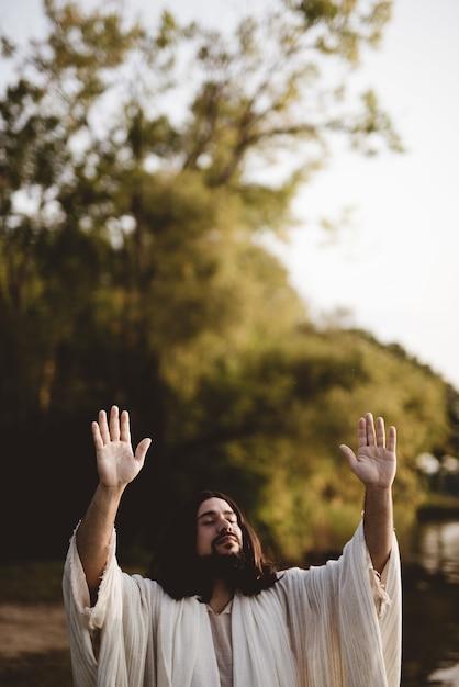 Gesù cristo con le sue mani verso il cielo mentre i suoi occhi sono chiusi Foto Gratuite