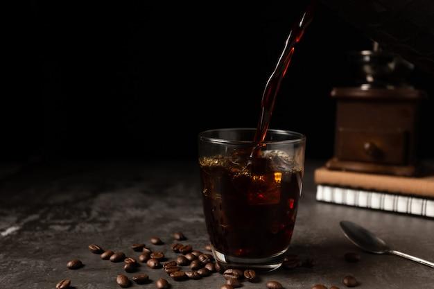 Ghiaccio caffè nero in un bicchiere sul tavolo di legno. Foto Gratuite