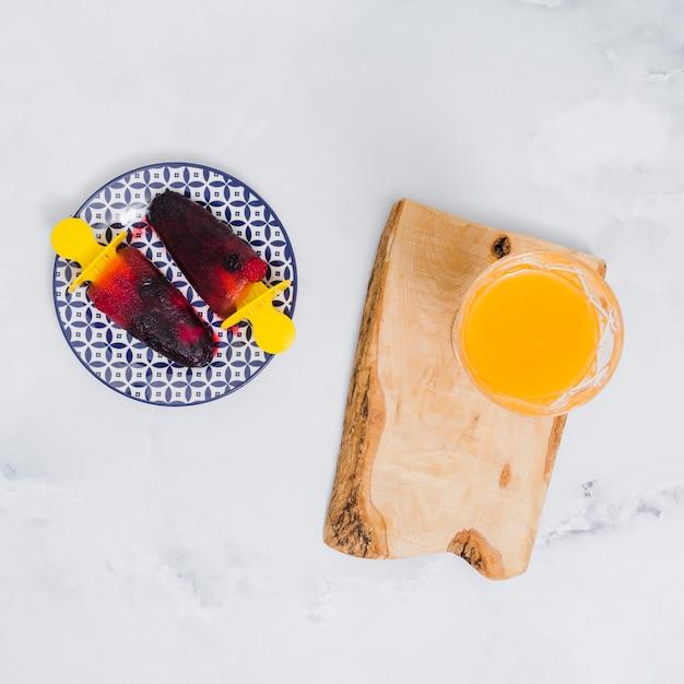 Ghiaccioli luminosi sul piatto e sul vetro con succo su supporto in legno su superficie grigia Foto Gratuite