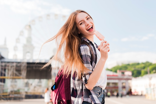 Ghiacciolo alla moda della tenuta della giovane donna con la bocca aperta Foto Gratuite