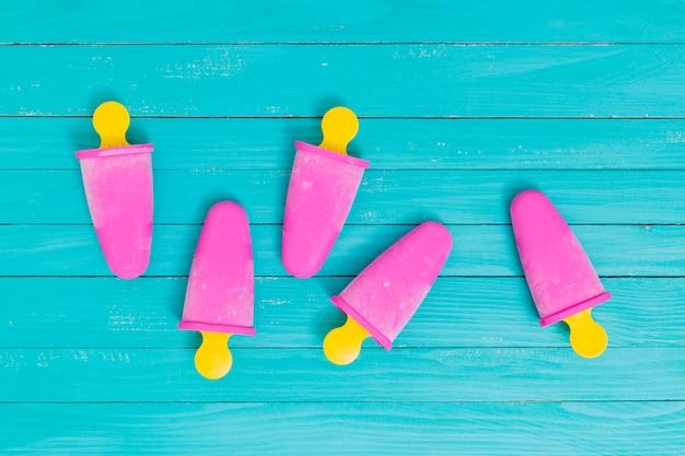 Ghiacciolo rosa su bastoncini gialli su superficie di legno Foto Gratuite