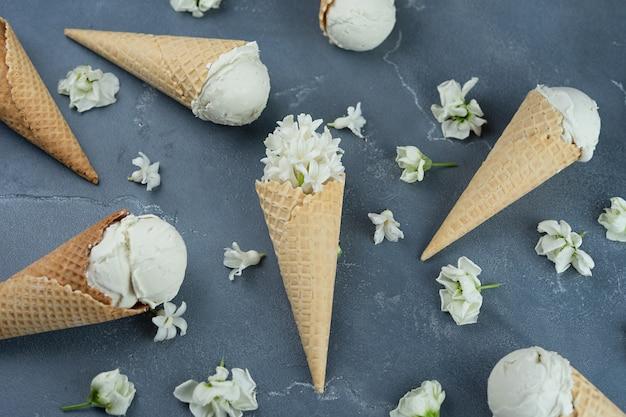Giacinto bianco e gelato alla vaniglia nei coni della cialda su fondo blu. concetto di modello Foto Premium