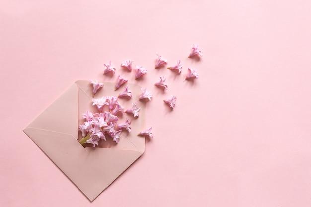 Giacinto rosa nella busta rosa sullo sfondo di carta Foto Premium