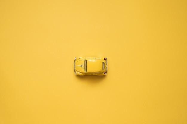 Giallo. auto giocattolo retrò su giallo ... concetto di viaggio estivo. taxi. vista dall'alto. Foto Premium