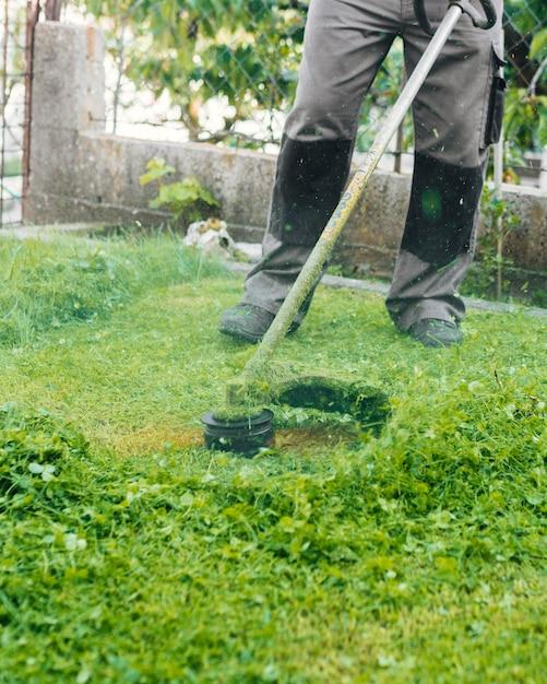 Giardiniere che falcia l'erba Foto Gratuite