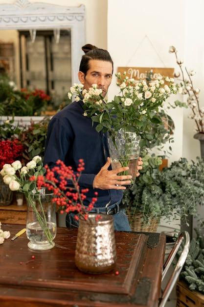 Giardiniere in possesso di un grande vaso di foglie e fiori Foto Gratuite