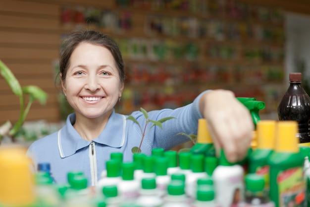 Giardiniere sceglie fertilizzante liquido in negozio Foto Gratuite