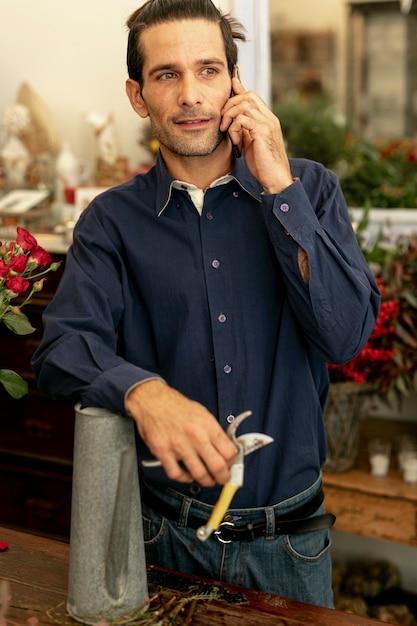 Giardiniere uomo con i capelli lunghi, parlando al telefono Foto Gratuite
