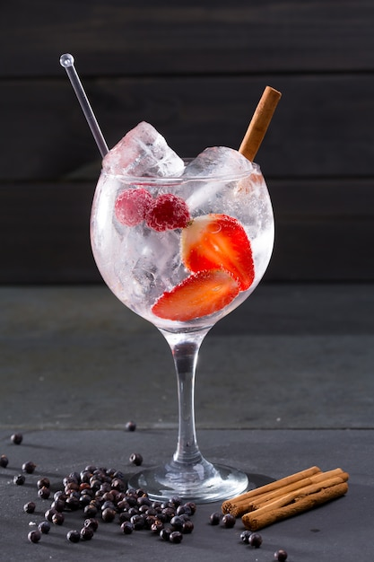Gin tonic cocktail con fragole alla cannella e ginepro Foto Premium