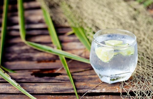 Gin tonic in vetro con cubetti di ghiaccio e fetta di lime Foto Premium