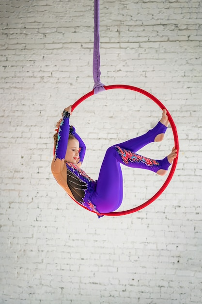 Ginnastica aerea sul cerchio, una bambina che fa gli esercizi Foto Premium