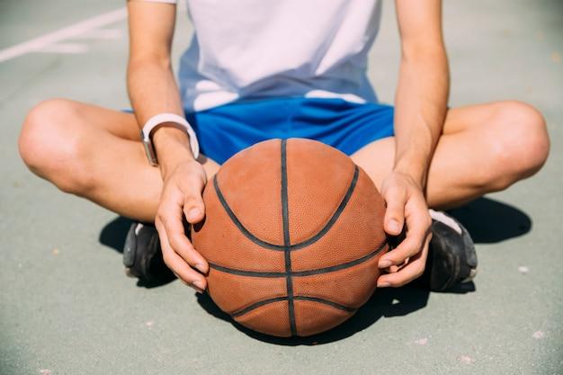 Giocatore che tiene pallacanestro mentre sedendosi sul campo da giuoco Foto Gratuite